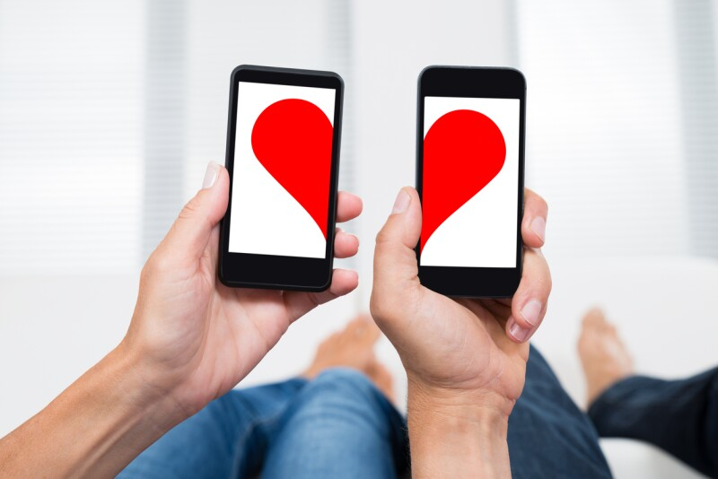 Two People With Mobile Phones Showing Halves Of Heart Shape