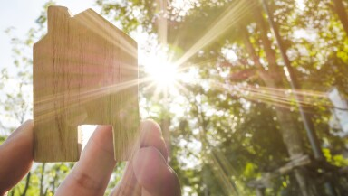Hand holding wooden house with green forest background blurred and sun lighting