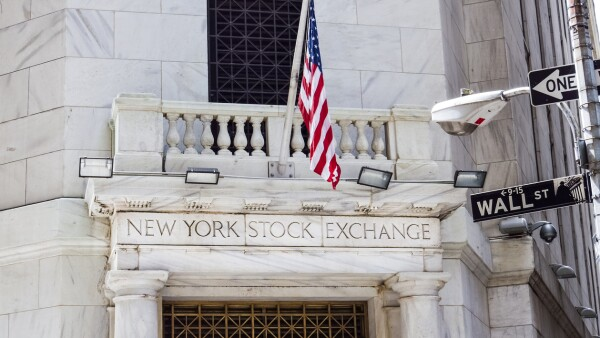 New York Stock Exchange with American flags and Wall street