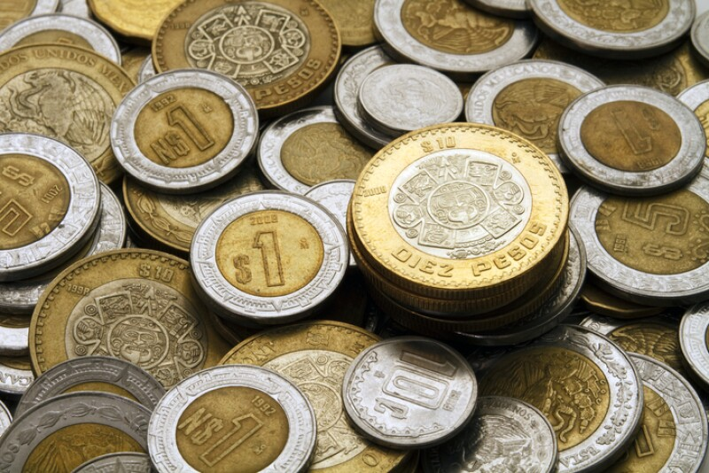 Ten Mexican Pesos Coin on a Pile of Coins