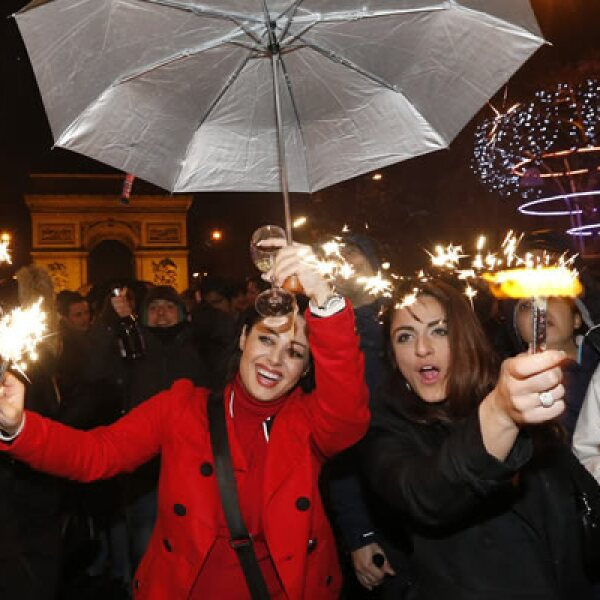 Un grupo de personajes festeja en París cantando y bailando.