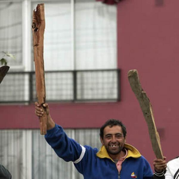Un grupo de hombres sostiene palos de madera con los que ahuyentan a posibles saqueadores