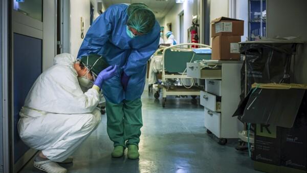 Una enfermera con máscara protectora y equipo conforta a otro mientras cambian de turno el 13 de marzo de 2020 en el hospital de Cremona, al sureste de Milán, Lombardía, durante el cierre del país destinado a detener la propagación de la pandemia del coronavirus.