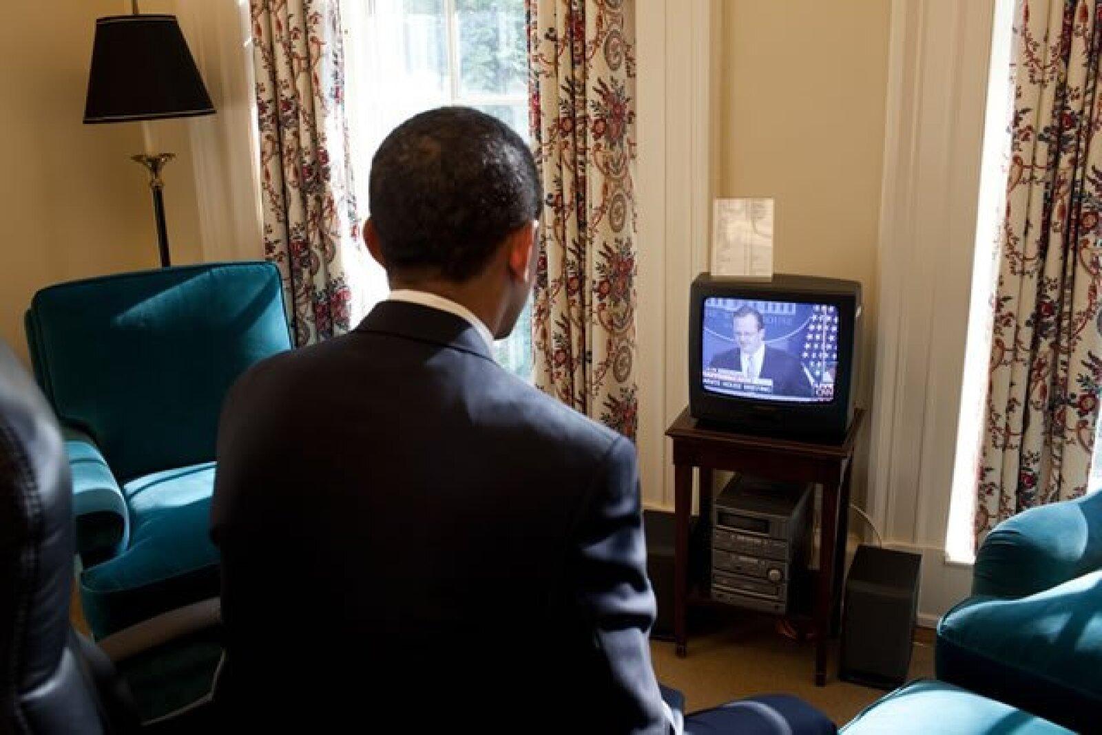 Obama observa en la televisión el primer informe del secretario de prensa en su estudio privado de la Oficina Oval.