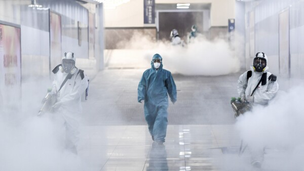 Volunteers in protective suits disinfect a railway station as the country is hit by an outbreak of the new coronavirus, in Changsha
