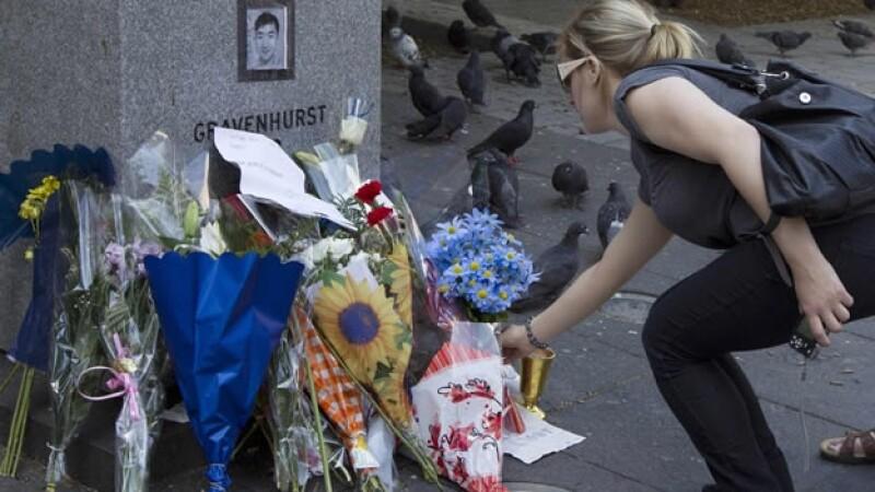 una mujer deja flores en un monumento de la universidad concordia