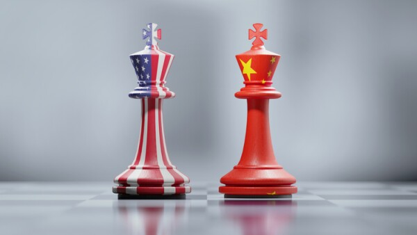 Two King Chess Pieces Textured With American And Chinese Flags On Black And White Chessboard
