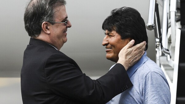 Bolivia's ousted President Evo Morales is welcomed by Mexico's Foreign Minister Marcelo Ebrard during his arrival to take asylum in Mexico, in Mexico City