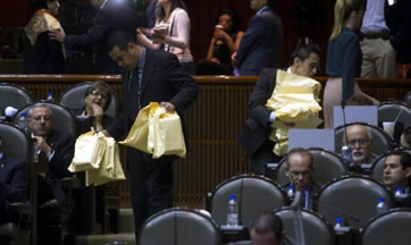 Asistentes llevan comida a los legisladores del PRI durante la sesión (Foto: Cuartoscuro)
