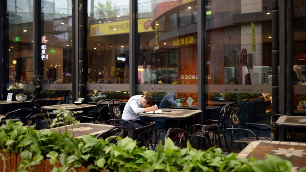 Man sits at a restaurant at a shopping complex in Beijing