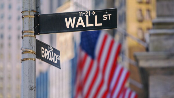 Wall Street Sign in New York With American Flags in the Background