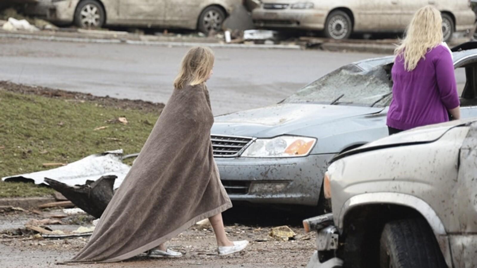 un niña con una cobija camina entre escombros