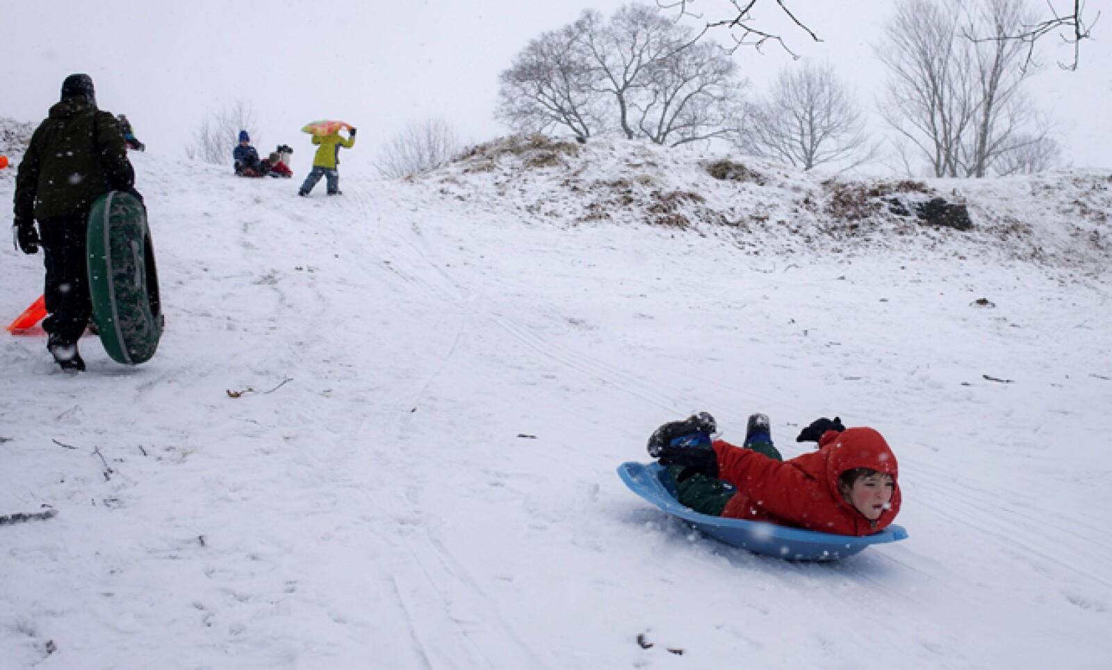 Reportes meteorológicos indican que esta podría ser la peor tormenta de nieve hasta ahora registrada. Un niño se desliza por una colina en Nueva York.