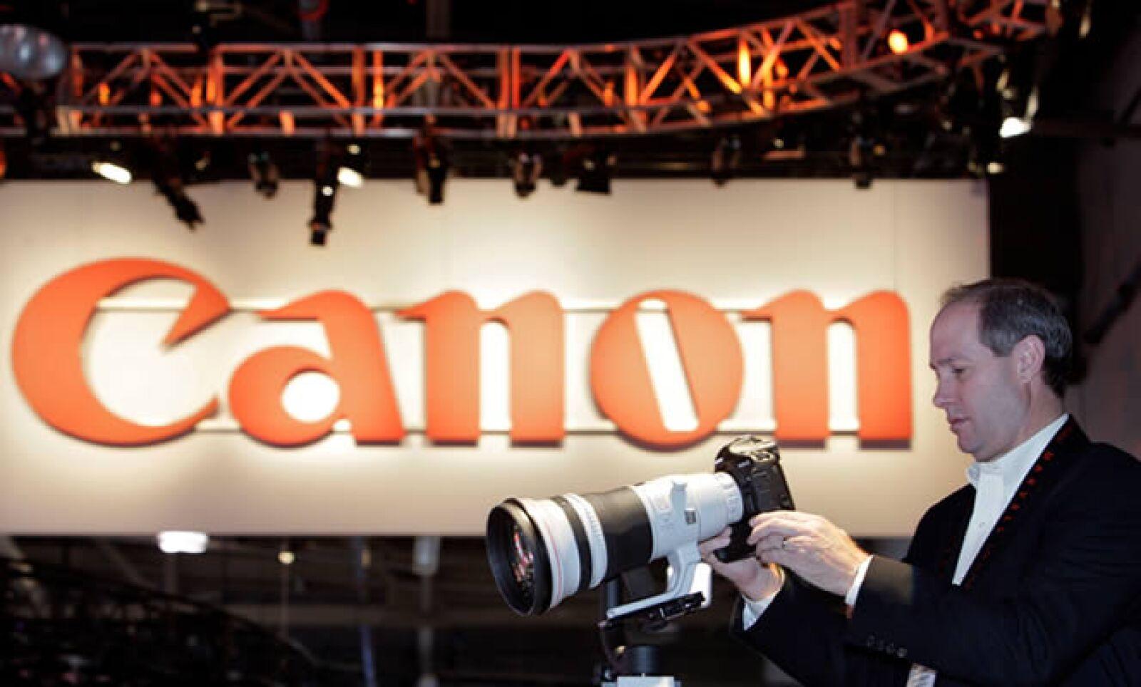 Un fotógrafo profesional visita el 'stand' de Canon, para apreciar su nueva cámara y telefoto de 400mm.