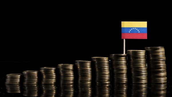 Venezuelan flag with lot of coins isolated on black background