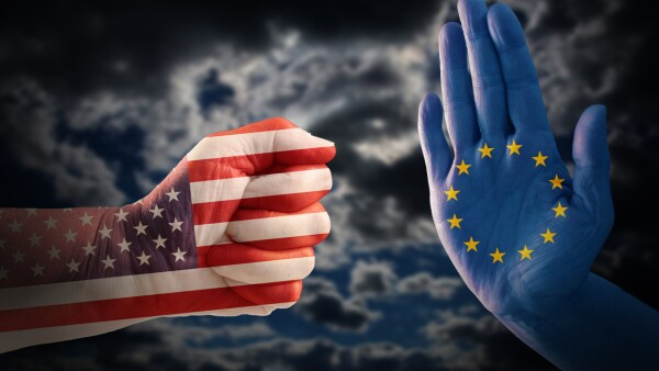trade conflict, fist with USA flag against a hand with European flag, dramatic cloudy sky in the background