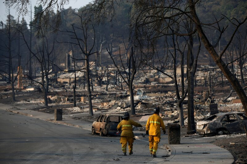 FILE PHOTO: Firefighters walk in a neighborhood destroyed by the Tubbs Fire in Santa Rosa, California