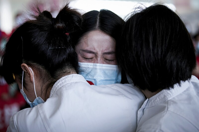 Medical workers hug at the Wuhan Tianhe International Airport