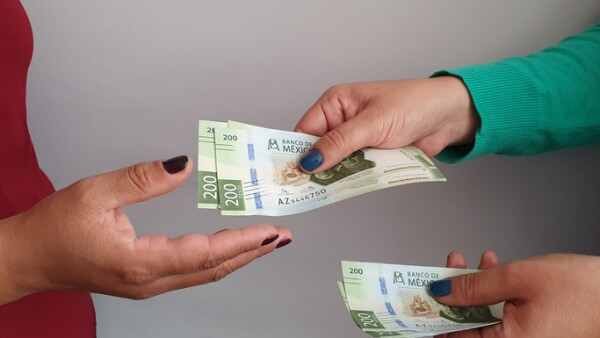 women hands paying and receiving mexican money