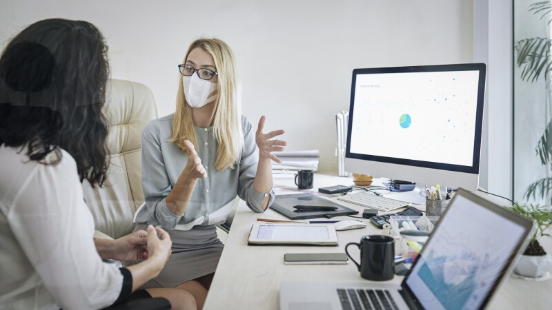 Businesswoman in medical mask explaining her idea