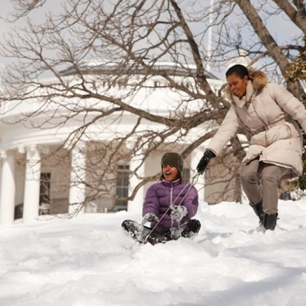 La primera dama y sus hijas, Malia y Sasha, se deslizan en la nieve en el South Lawn de la Casa Blanca.