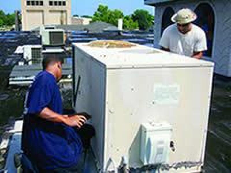 Dos trabajadores reinstalan una unidad de 5 toneladas despu�s de repararla. El mantenimiento preventivo de las unidades de aire acondicionado pudo evitar este gasto innecesario.