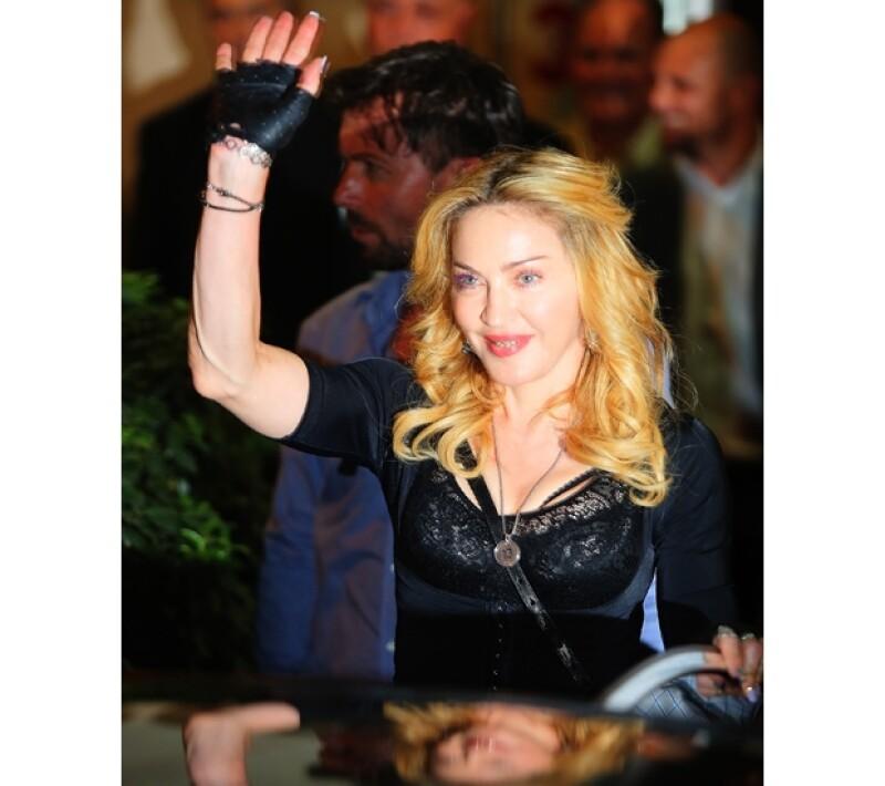 La reina del pop visitó este miércoles lo que será una sucursal de su cadena de gimnasios Hard Candy ubicada en la capital italiana. La cantante llamó la atención por su brillante dentadura.