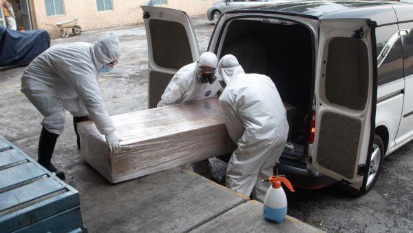 Cremadores cargan un ataúd de una muerte a causa de Covid-19 en el Velatorio San Isidro