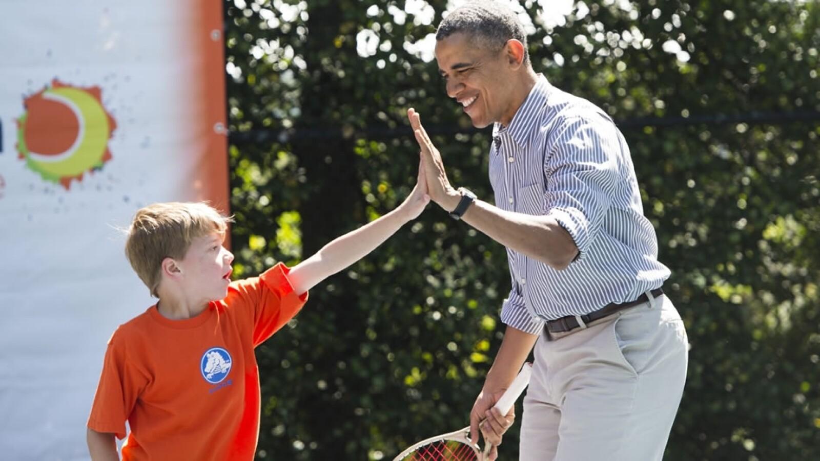 Barack Obama festeja con un niño que fue su compañero de equipo tras una partida de tenis