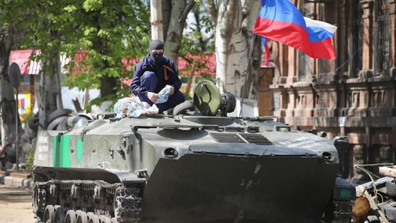 Un militante prorruso sentado sobre un vehículo armado en frente de un edificio ocupado del Servicio Secreto de Ucrania en Slovyansk