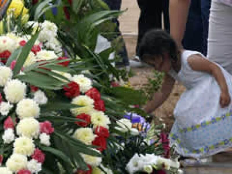 Ua pequeña deposita una flor durante el entierro de las víctimas del incendio. (Foto: Reuters)