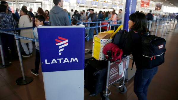 FILE PHOTO: Passengers wait to check in for their flights at the departure area of Latam airlines inside of the Commodore Arturo Merino Benitez International Airport in Santiago