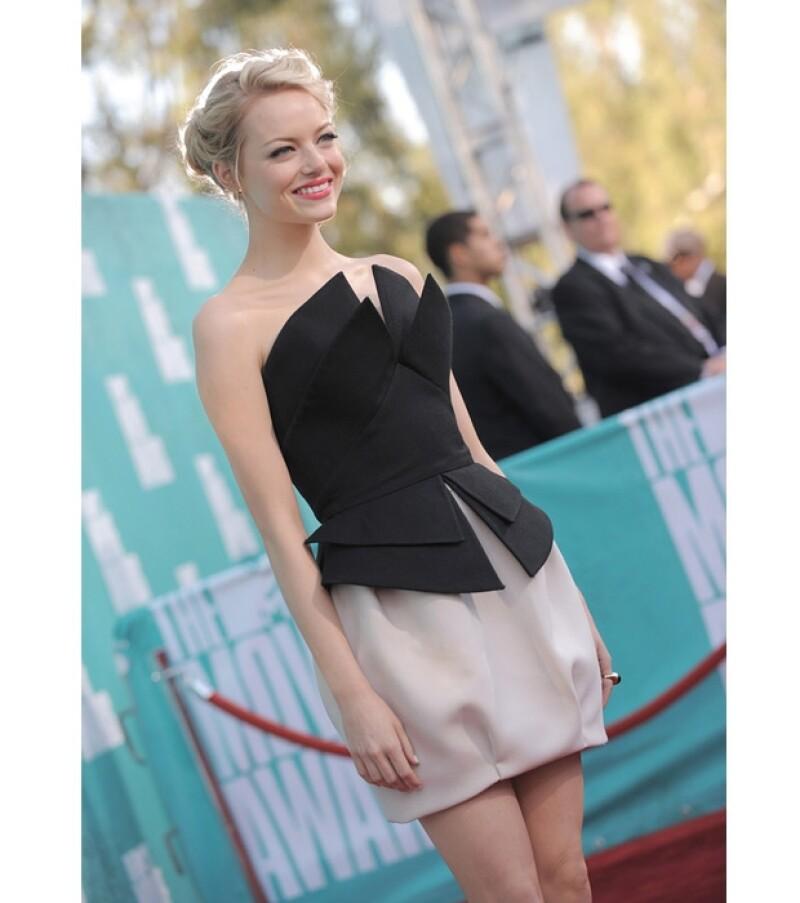 Emma Stone preocupada por acomodarse el vestido antes de desfilar por la alfombra a las afueras del anfiteatro Gibson en los Estudios Unviersal.