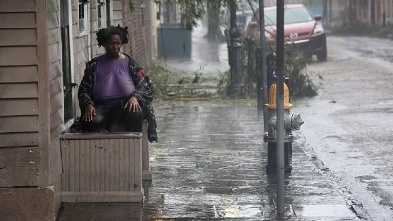 una mujer observa la lluvia sentada en una banca