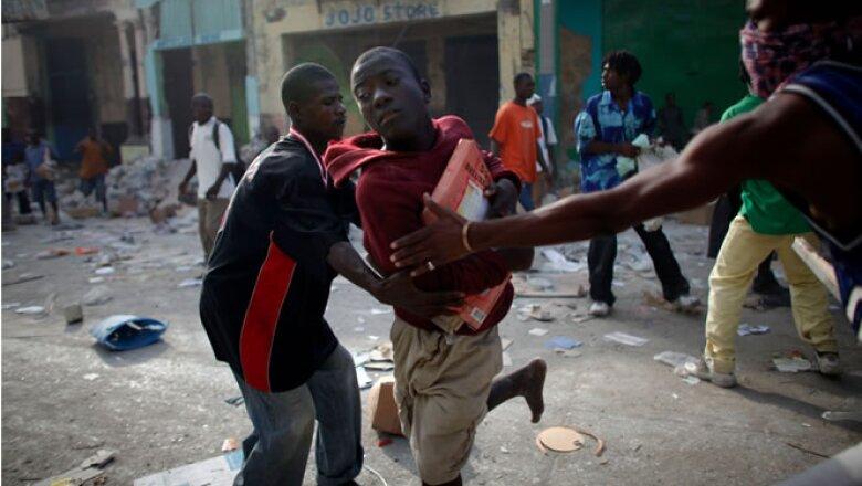 Los habitantes de Puerto Príncipe luchan entre sí por agua, comida o cualquier producto que puedan utilizar y que se halle entre los escombros. A cuatro días del sismo, la ayuda recibida es insuficiente.