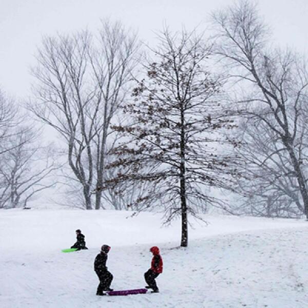 Algunos niños aprovechan la acumulación de nieve para jugar.