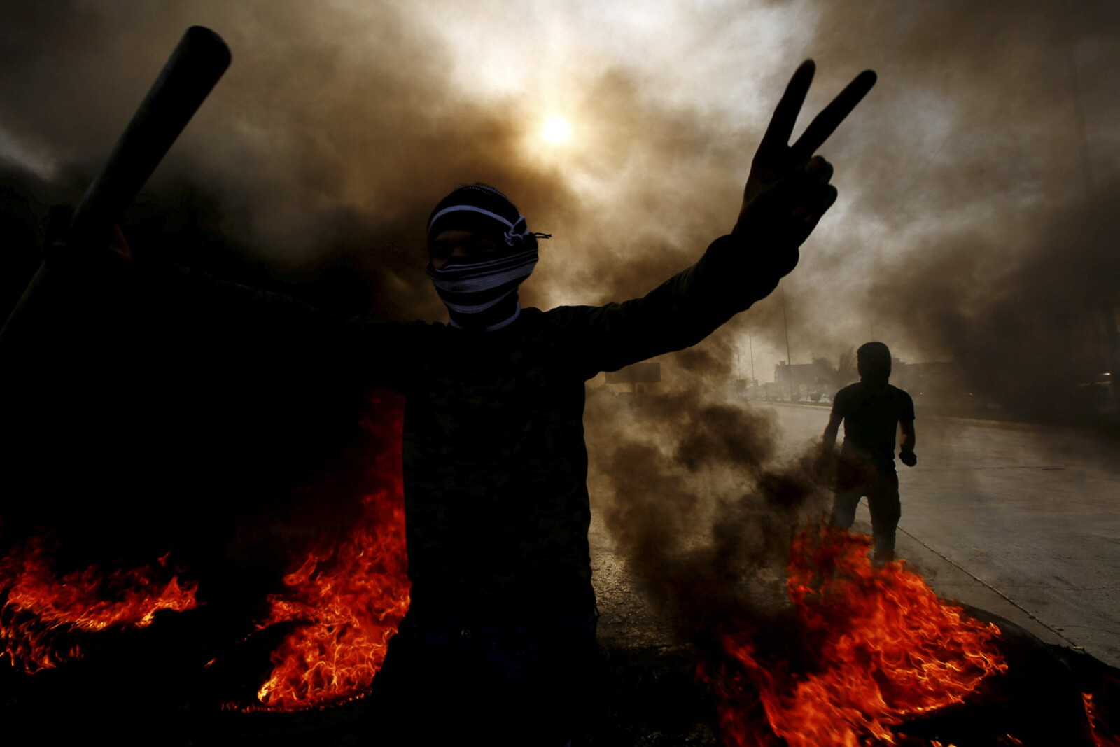 An Iraqi demonstrator gestures near burning tires to block a road during ongoing anti-government protests in Najaf