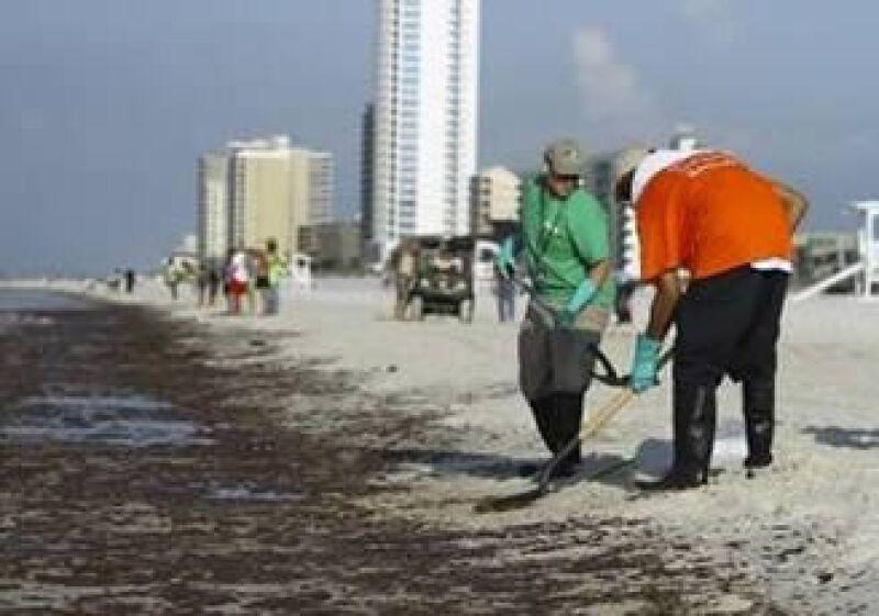Personas limpian el crudo que ha llegado a costas de Alabama. (Foto: Reuters)