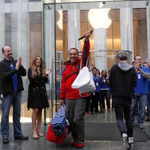 Uno de los primeros compradores sale de una tienda de Apple, entre aplausos de empleados y fanáticos.