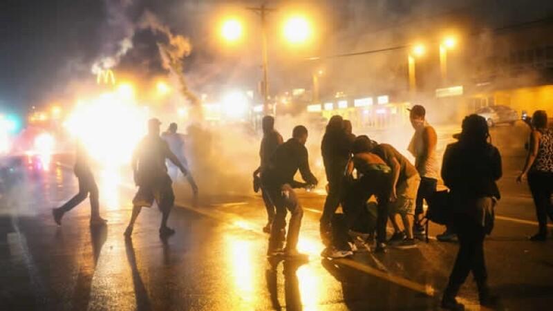 Un grupo de manifestantes resiste los ataques de la policía durante una protesta por la muerte de un joven negro en Ferguson