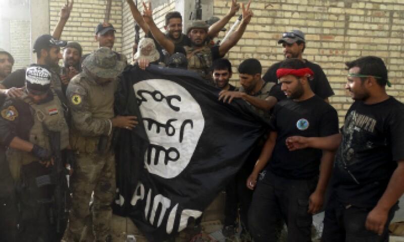 Fuerzas iraquíes sostienen una bAndera de ISIS. (Foto: Reuters)