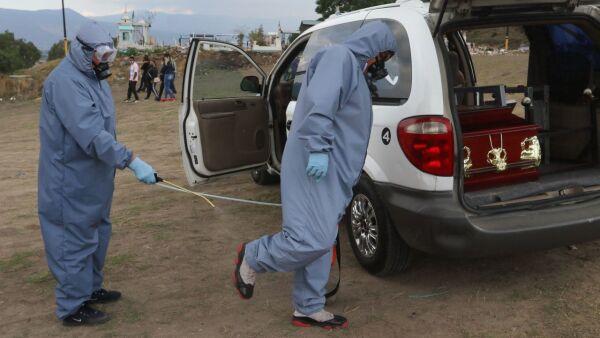 Dos trabajadores de Funeraria se sanitizaron después previo a realizar una inhumación de una muerte por probable Covid-19 en el Panteón Municipal Xico