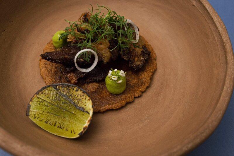 Taco de cachete con cilantro, aguacate y cebolla