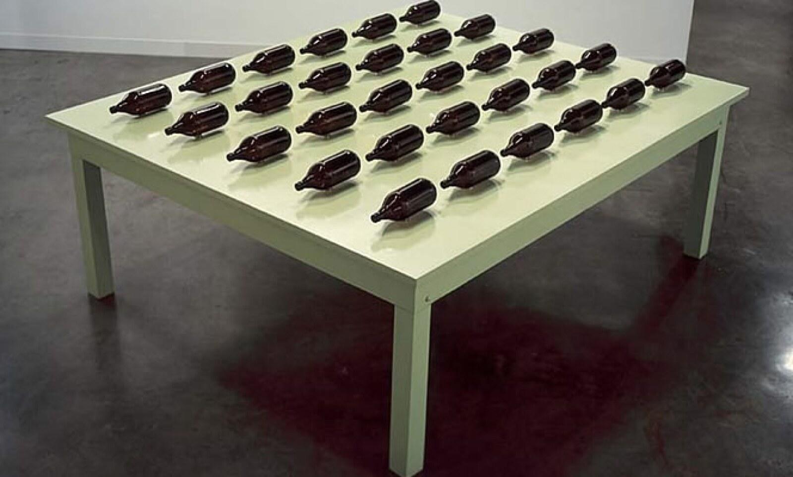 La obra de Rafael Lozano-Hemmer presenta a 30 botellas de vidrio sobre mesa de madera motorizada y controlada por algoritmos de simulacion neuronal.