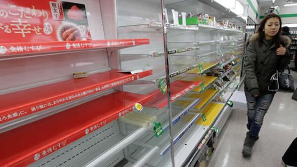 Una mujer busca provisiones en una tienda de Tokio, a pesar de que las tiendas muestran muy poca comida y agua.