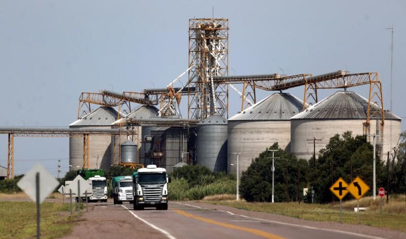 FILE PHOTO: Trucks pass by grain silos near Ceres