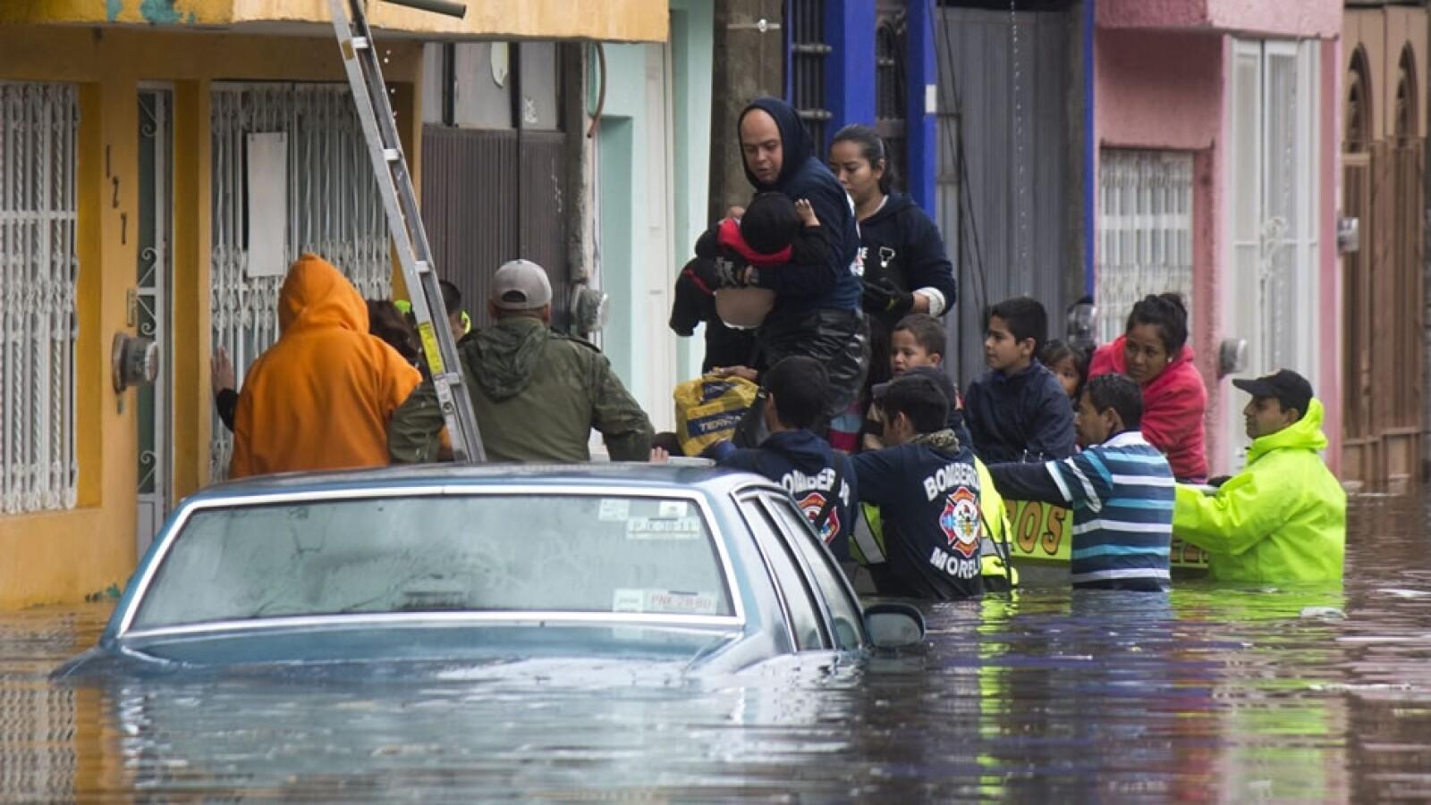 Elementos de Protección Civil y bomberos realizaron maniobras de rescate a familias afectadas por las lluvias de este domingo en Michoacán