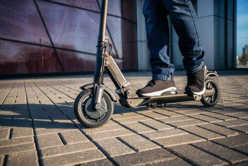 Close up view of legs of man on electric scooter