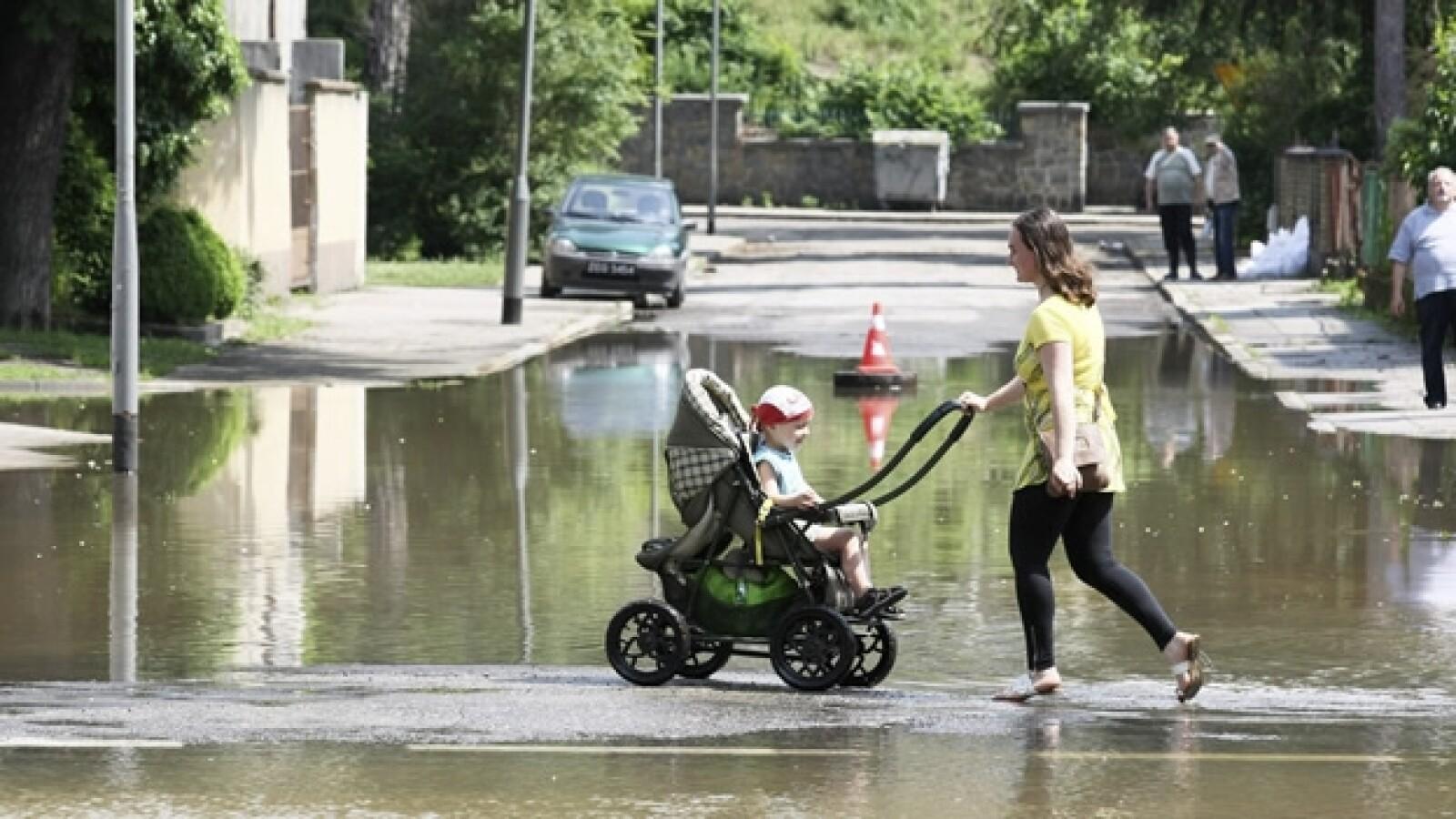 una madre atraviesa una calle inundada con su hijo
