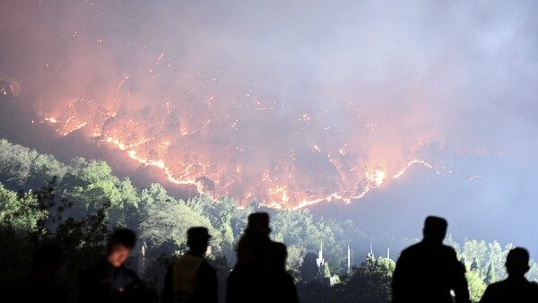 Firefighters work on extinguishing a forest fire that started near Xichang in Liangshan Yi Autonomous Prefecture of Sichuan province